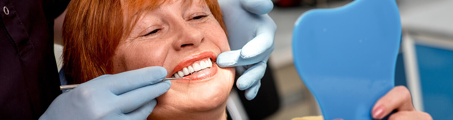 woman with short red hair getting a teeth cleaning at the dentist