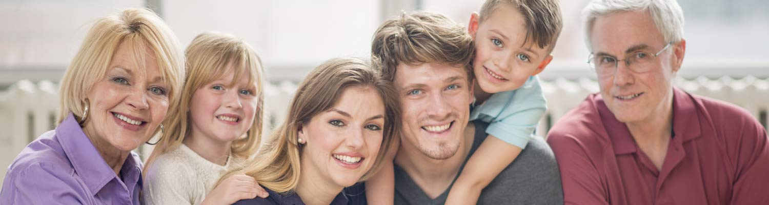 Multigenerational family smiling and showing off beautiful, healthy teeth.