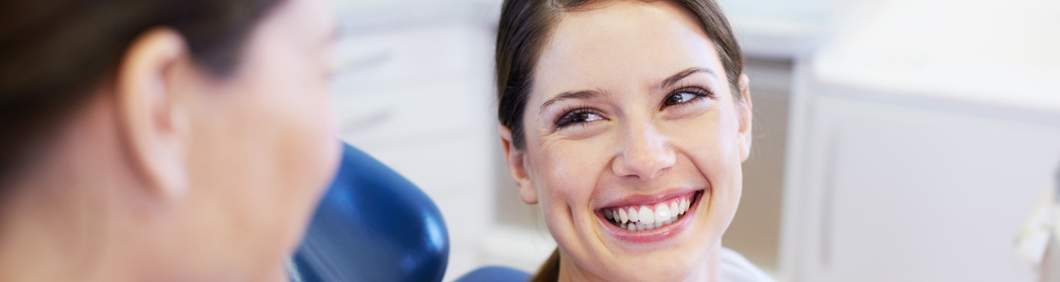 woman smiling after her easy, pain-free tooth extraction