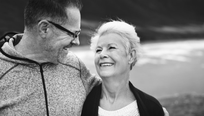 elderly couple arm in arm smile at each other