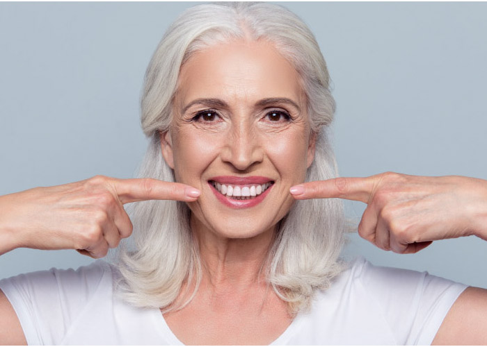 white haired woman pointing at her beautiful smile with both forefingers