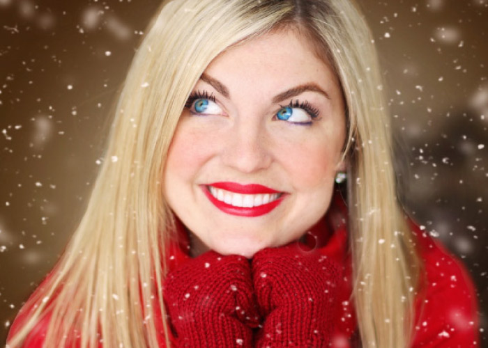 blond, blue eyed girl wearing a red sweater and gloves smiles to show off her porcelain veneers and snow comes down
