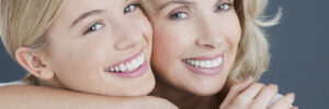 two blond women hug and smile after cosmetic dentistry