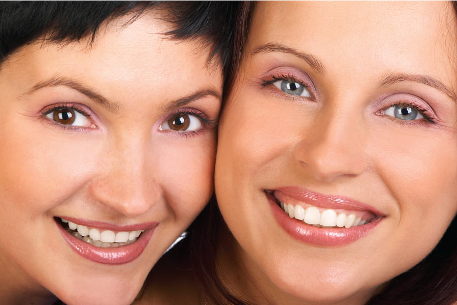 close up of two women smiling showing off their smiles