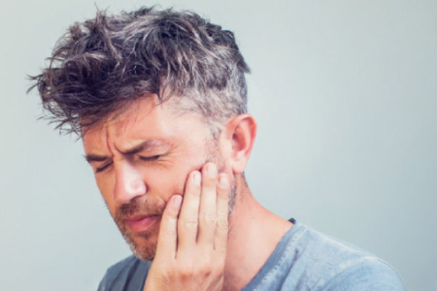 man holds his jaw in pain with a tooth infection