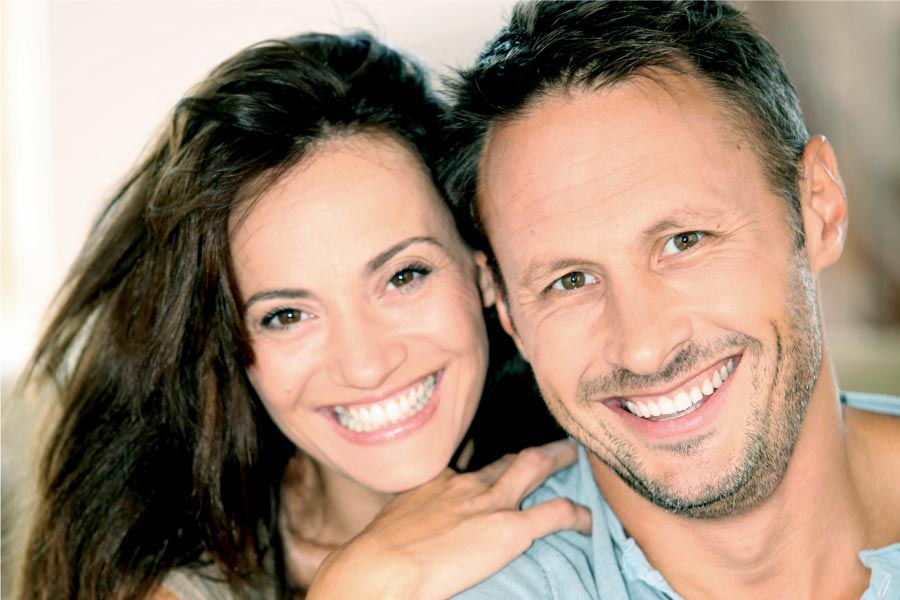 young couple smile showing off their porcelain veneers