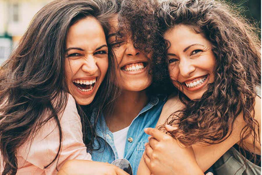 three young women smile showing off their teeth