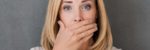 woman covers her mouth to hide receding gums