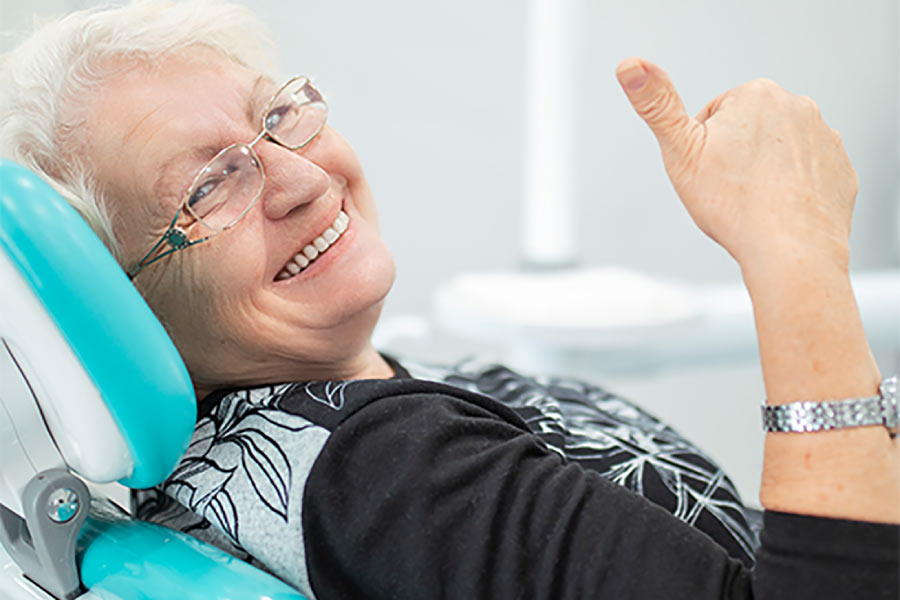senior woman gives a thumbs up while sitting in the dentist chair