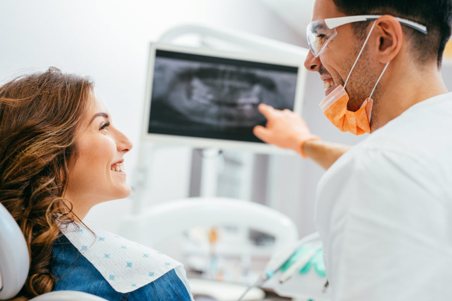 woman looks at x-rays with the dentist to identify cavities or stains on teeth